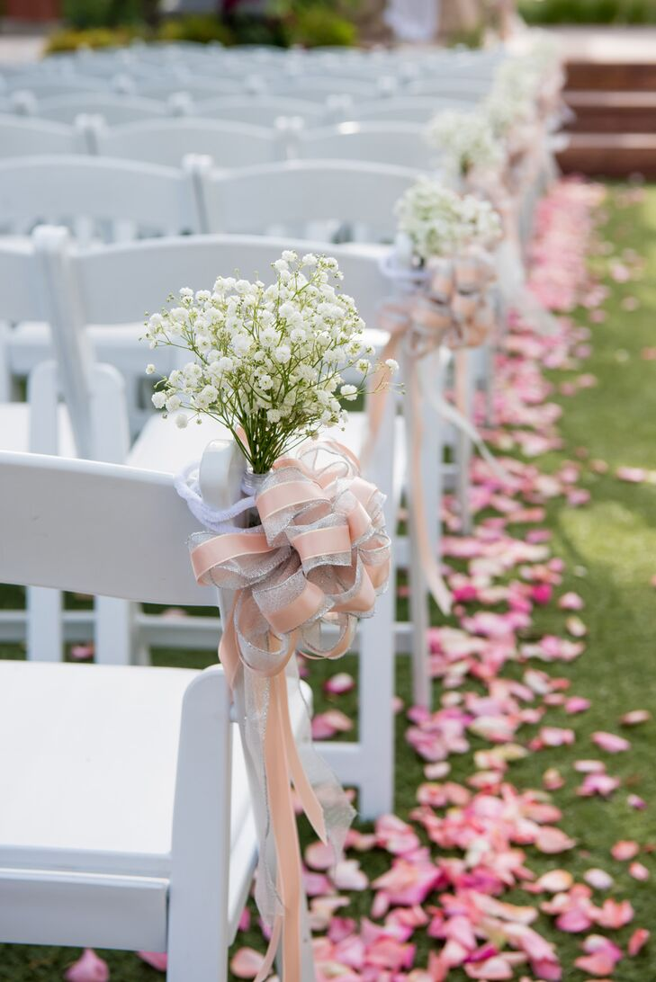 Pink rose petals were scattered down the sides of the aisle, giant pink bows and baby's breath were tied on aisle seats, and bouquets were placed on the altar.