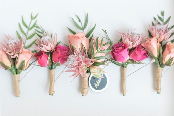 Mirroring the wedding's bright pink and coral colors, the groomsmen had boutonnieres made with roses and sprigs of green ferns.