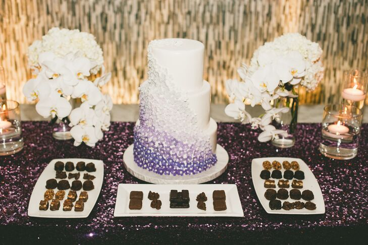 Playing off the ceremony's ombre rose petal-lined aisle, the couple's three-tier wedding cake featured a cascade of purple ombre sugar flowers.
