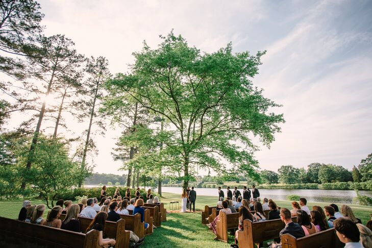 Madelyn and Joseph exchanged their vows under a tree wrapped with greenery and florals. A chandelier overhead and a vintage rug under them created a romantic, boho niche. Their guests sat lakeside in vintage wooden church pews.