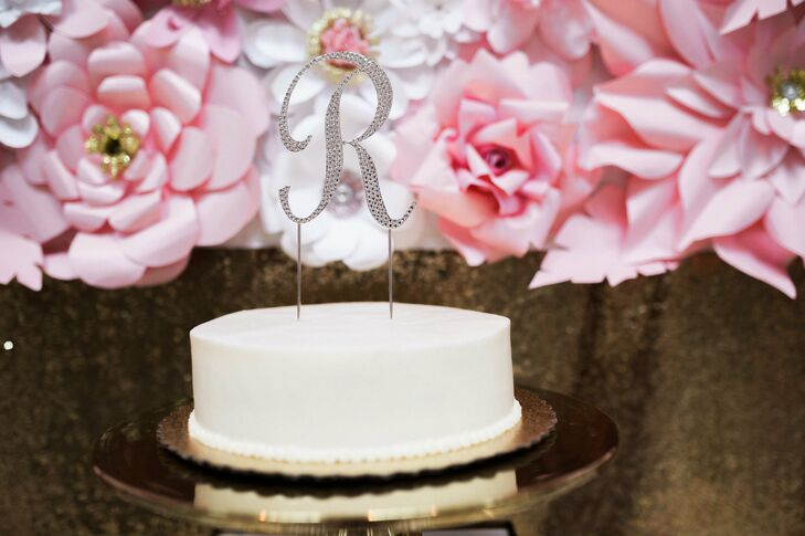"""The couple looked to their matching first-name initial to create a glistening """"R"""" to top their simple white cake."""