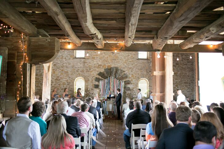 """Megan and Marcus exchanged vows at Historic Taylor Barn in Lawrence, Kansas. """"The historic farm was so picturesque and characteristic of our Midwest upbringings,"""" Megan says. The backdrop was designed and built by Marcus and included an antique windmill blade, lace donated from the nuns at Megan's church and scraps of fabric from the napkins Marcus's mother made for the wedding."""