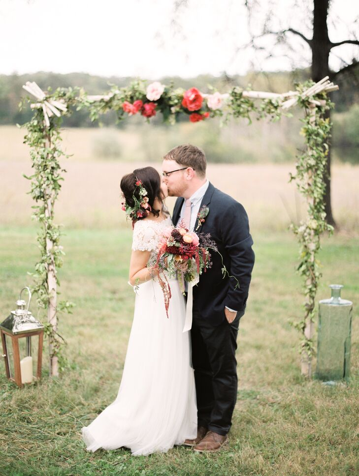 Vine-Covered Wedding Arch with Red Peonies
