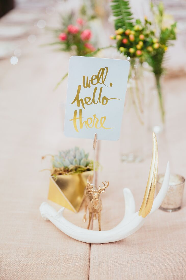 "Mai and Brian crafted gold deer figurines to mark each table at the reception at Ace Hotel & Swim Club in Palm Springs, California. Each was paired with a gold-dipped antler decoration and a ""well, hello there"" paper sign with gold lettering."