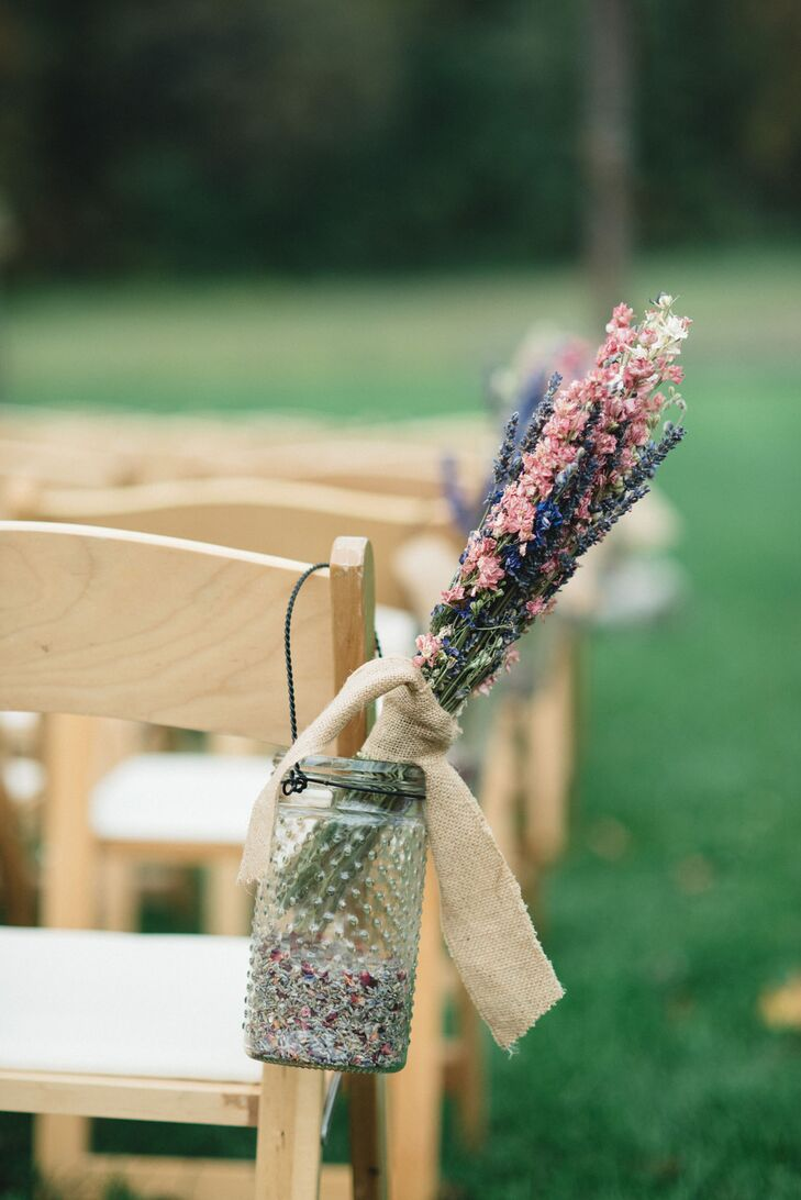 At the ceremony, folding chairs had glass mason jars filled with arrangements of dried flowers decorating the aisle.