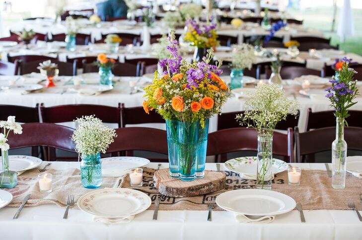 Aside from the wedding party's looks, Sarah and Sean didn't want a specific palette. So they filled the reception with an explosion of color. Each family-style table was filled with bright wildflowers, roses and delphiniums in blue glass or clear bulb vases that were personally collected by Sarah.