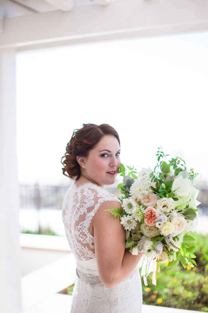 Bayley wore an ivory lace wedding dress accented with a crystal belt. She held a lush flower bouquet filled with scabiosa, garden roses, and dahlias accented with veronica and leaves.