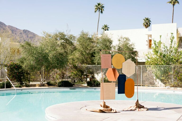 Colorful geometric seating chart at poolside Palm Springs wedding