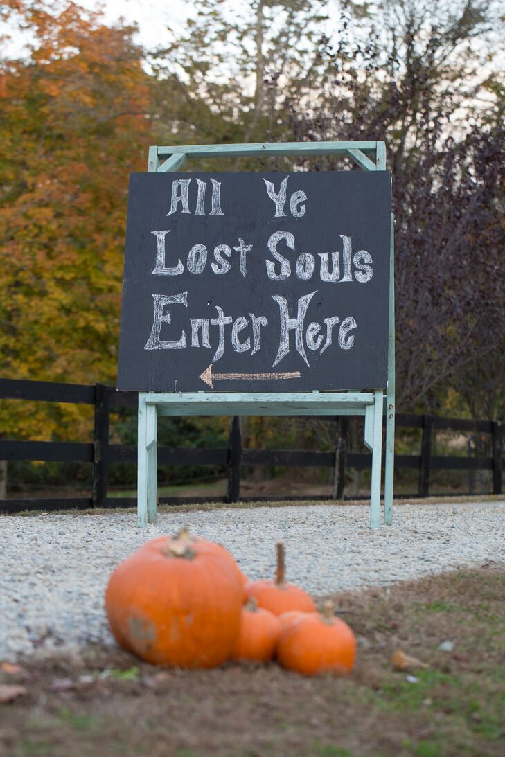 A chalkboard sign directed guests to the costume-party reception with a Halloween message.
