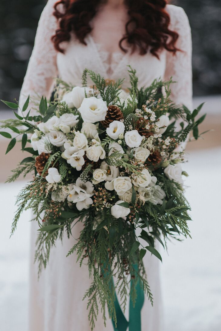 "Lake Placid Flower and Gift fashioned Cait's winter-fresh bouquet. ""I really wanted tons of greenery, natural, woodsy elements and organic white flowers,"" says Cait, whose bouquet and other arrangements for the day incorporated pine cones, cedar, birch, as well as magnolia, white ranunculus, lisianthus and wax flowers."