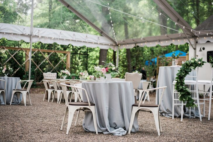 Under the clear-top tent, dining and cocktail tables were clad in gray linens and topped with an array of floral arrangements and potted herbs for the reception at the Parlour at Manns Chapel in Chapel Hill, North Carolina.