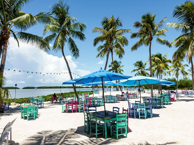 Tables with umbrellas on the beach with palm trees