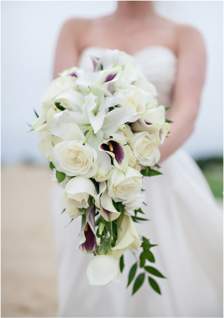 Carrie opted for a dramatic cascading bouquet filled with ivory roses and lilies. The addition of Picasso calla lilies added a subtle hint of color that tied into the day's purple color scheme.