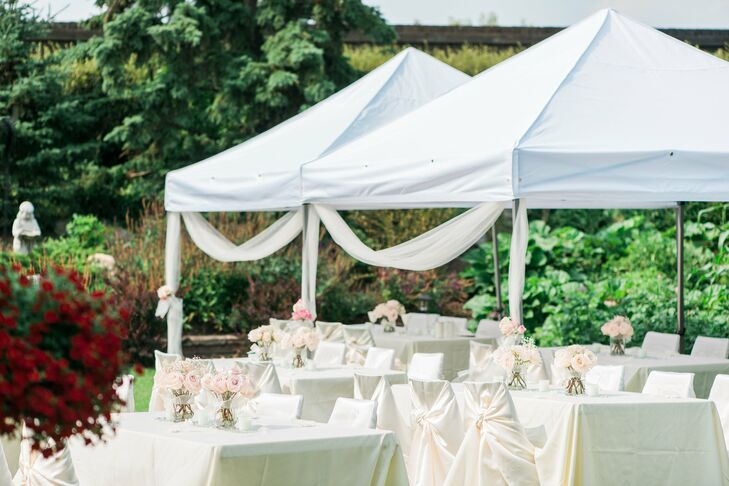 A white tent half covered the white linen tables for the backyard reception.