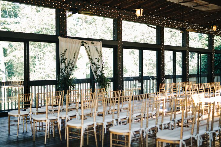 Indoor Ceremony in front of Draped Arbor with Greenery