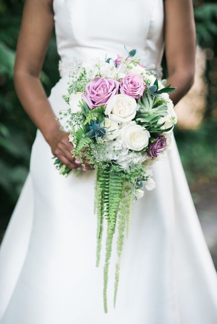 Joy carried a bouquet of blush and white roses and hanging green cattails. It was topped with a satin wrap accented in crystals.