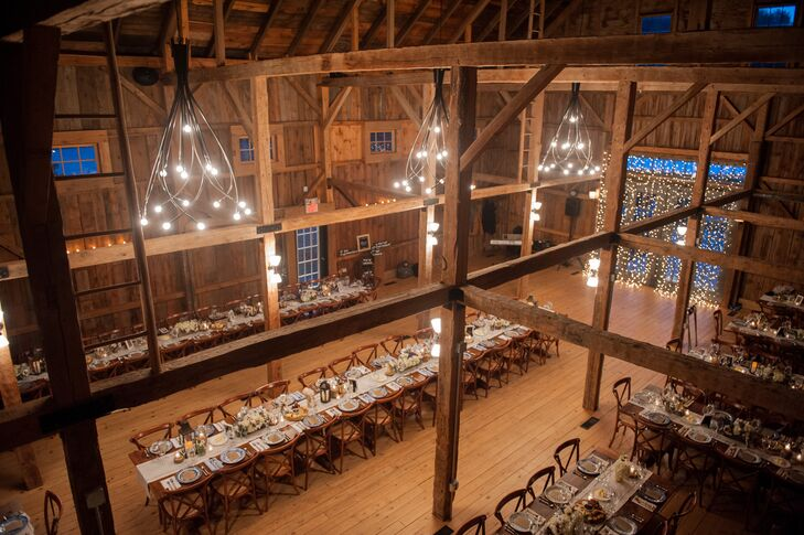 """After the """"I dos,"""" Jill and Donal whisked guests off to Flanagan Farm's wooden barn for a night of dinner and dancing. While the barn's lofty cathedral ceilings were downright awe inspiring, the use of wooden farm tables, vintage dinnerware, linen table runners and votive candles gave the space a warm, inviting ambiance."""