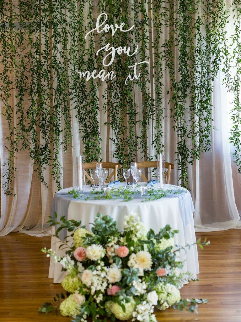 Curtain of hanging vines with neon sign behind sweetheart table at wedding reception