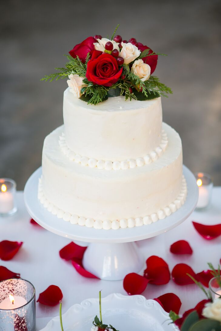 The two-tiered wedding cake was beaded at the bottom of each tier and topped with ivory and red roses. The cake was positioned on a white stand surrounded by red rose petals and lit candles.
