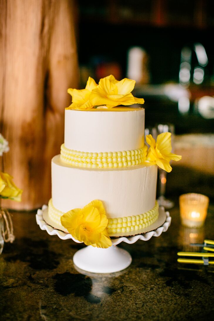 """A few gladiolus and yellow fondant beads accented the simple two-tier buttercream cake. """"I went with fresh flowers because I loved the element of realness they added,"""" Charita says."""