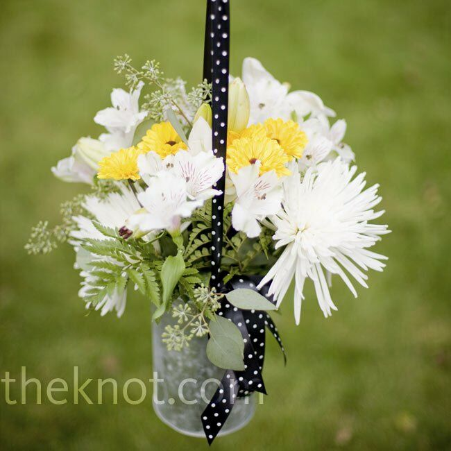 In keeping with the garden party vibe, simple white and yellow arrangements lined the aisle. The mums, lilies, alstroemeria and mini sunflower cushions hung in galvanized buckets from shepherd's hooks via black-and-white polka-dot ribbon.