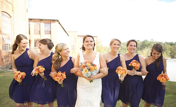 The bridesmaids picked out one-shoulder navy chiffon Donna Morgan dresses from J. Andrew's Bridal + Formal to tie in to the blue wedding color. They also wore cowboy boots for Nicole and Brandon's shabby-chic wedding.