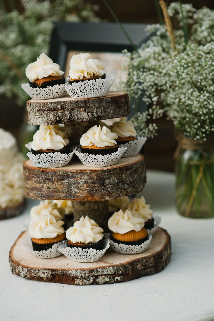 Small vanilla frosted cupcakes were displayed on a tree slice tower.
