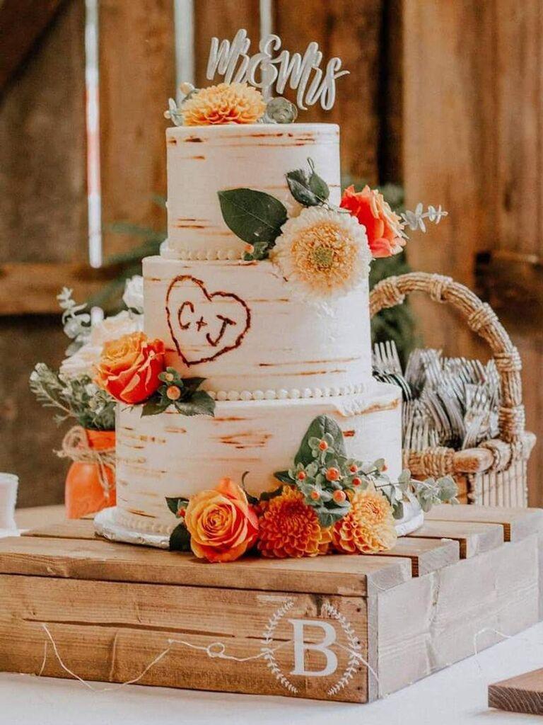 Semi-naked wedding cake on wooden monogram square cake stand