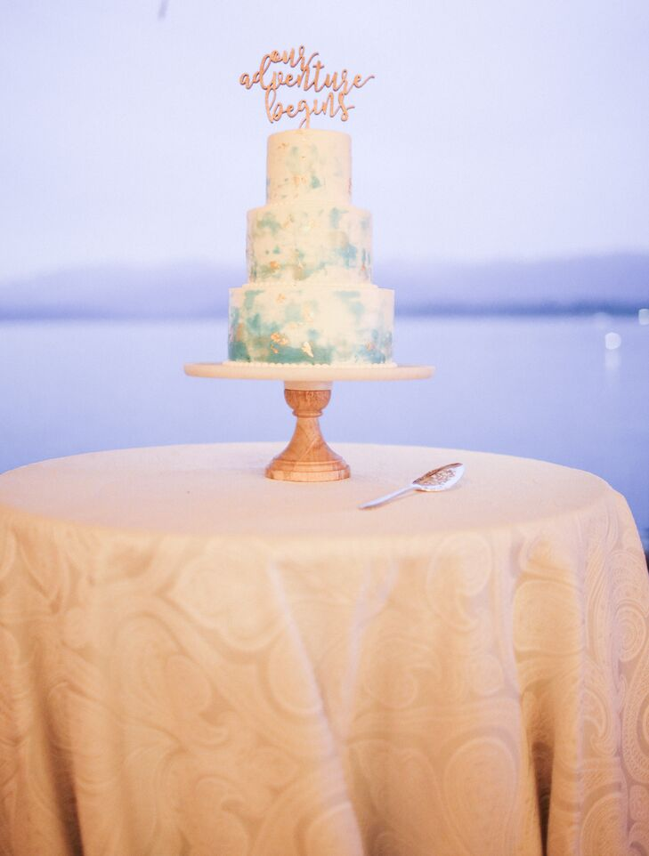 "Greg Marsh Designer Cakes created the couple's peach and ivory watercolor cake, which was topped with the phrase ""Our adventure begins."""