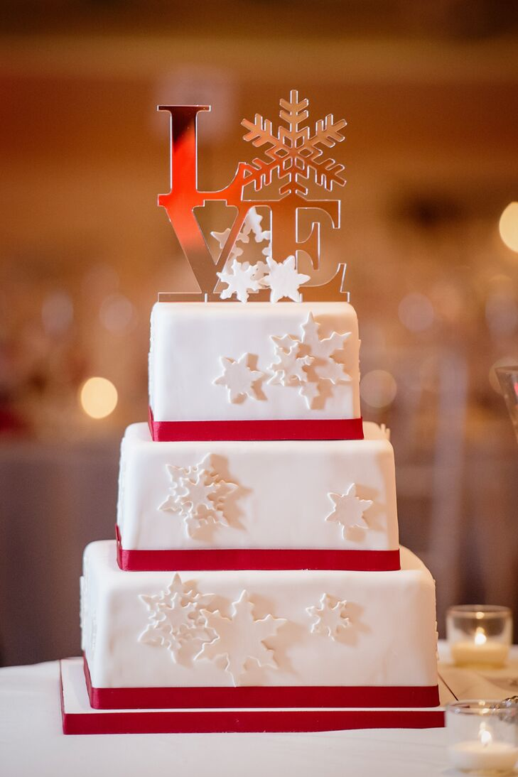 "The square tiered cake, created by Charm City Cakes, had three flavors: almond amaretto, mint chocolate and pumpkin cinnamon. Fondant snowflakes and red ribbon decorated the exterior and the creation came topped with a winter-y version of the famous ""Love"" sculpture."
