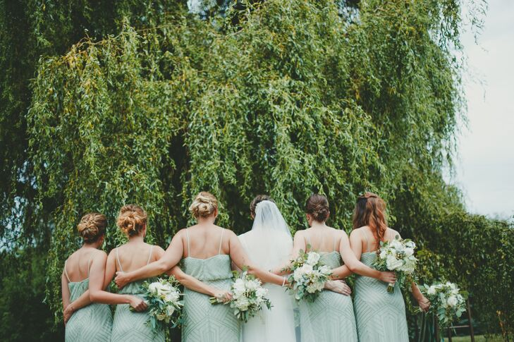 The bridesmaids wore sage-colored dresses from BHLDN and carried ivory and green bouquets similar to Natalie's.