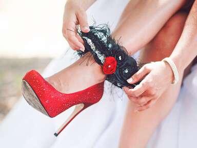 Bride putting on black and red wedding garter