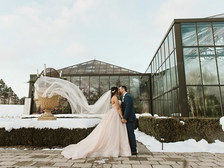 Bride and groom kissing on wedding day at outdoor venue with veil blowing in the wind