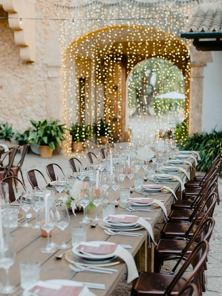 Outdoor wedding reception tables with curtain string lights hanging from arch