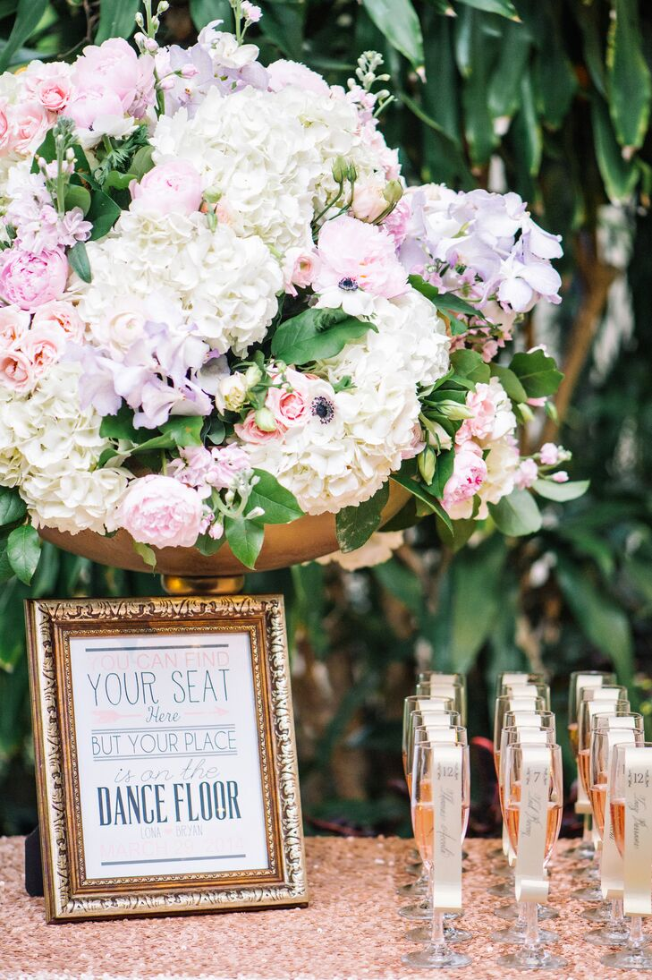 """The escort card table was decorated with a sign that read, """"You can find your seat here, but your place is on the dance floor"""", and a gold vase full of hydrangea, ranunculus, anemones, peonies and roses."""