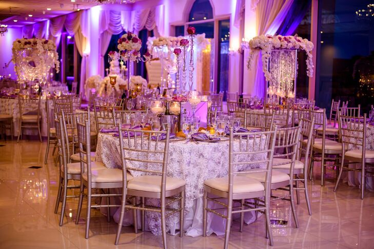 """Nkenna and Ekwere overlooked no detail when it came to the reception at Greentree Country Club in New Rochelle, New York. Floral lace linens, skyward-reaching arrangements of orchids with cascades of shimmering crystals and brightly lit candles paired with purple uplighting for a glamorous, showstopping scene. """"I wanted my guests to be wowed by the decor,"""" Nkenna says. Mission accomplished."""