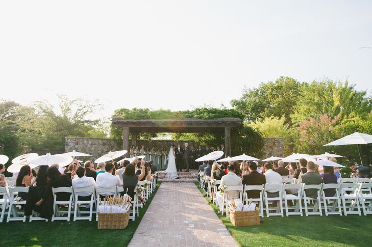 "Before kicking the celebration into high gear, Jessica and Brent gathered their guests in the gardens at the Vintage Estate, where they shared moving ""I dos"" under a canopy of cascading vines. A quaint brick path served as the ceremony aisle, which was lined with bunches of ivory and pink roses arranged in vintage-inspired glass jars. The pair provided playful white parasols at the entrance of the ceremony to help guests keep cool in the warm summer sun."