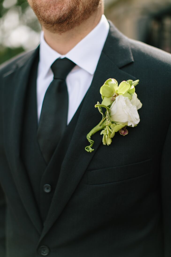 She's My Florist designed a white rose boutonniere surrounded by greenery.