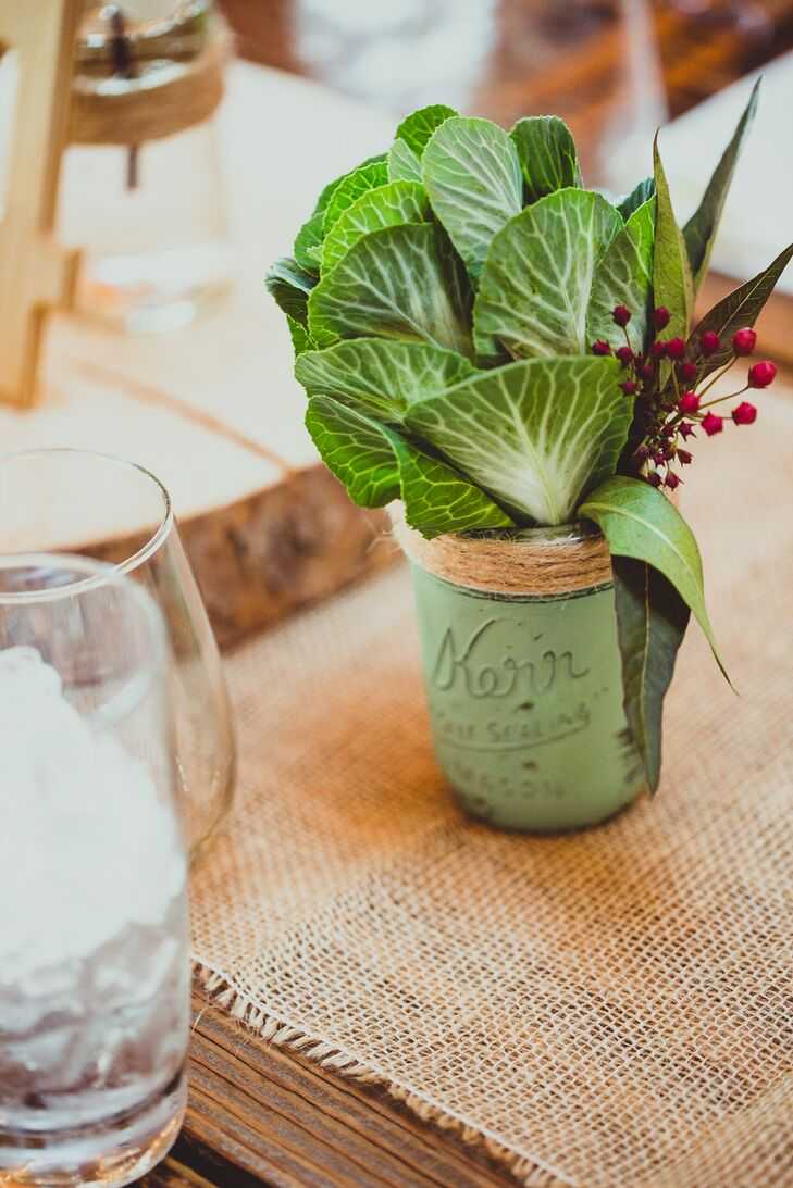 Green plant leaves accented with berries were placed in green painted mason jars for centerpieces.