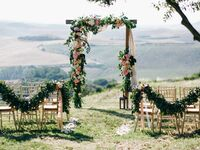Altar at outdoor wedding ceremony with floral arch