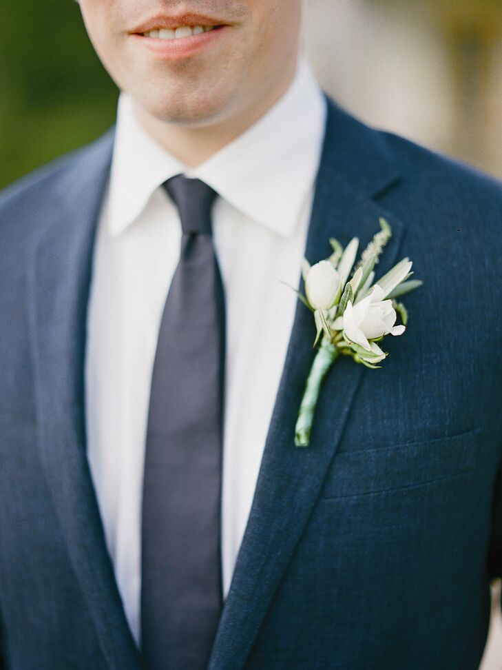 A green and white boutonniere of rose buds, olive leaves, rosemary and viburnum berries popped against Brandon's navy lapel.