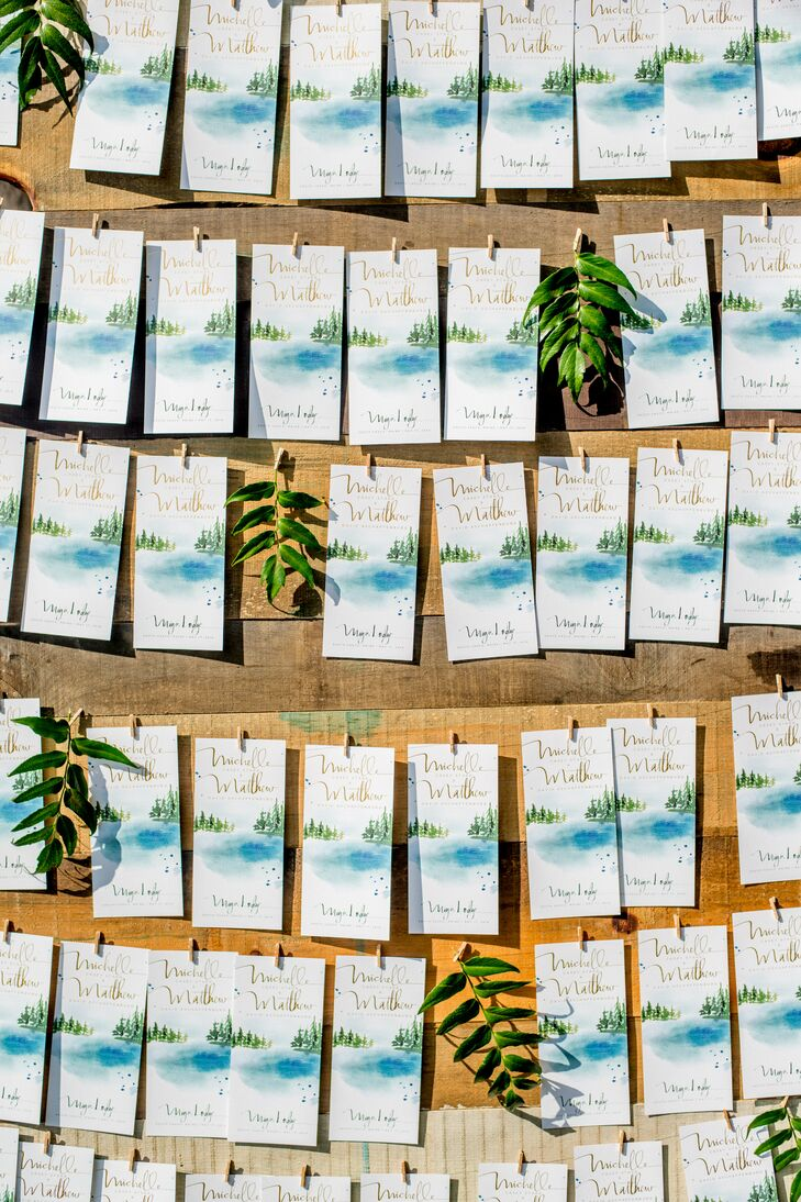 "With the help of MStarr Event Design, Michelle and Matt planned a cheerful, rustic affair filled with details that captured the essence of Maine's natural beauty, while telling the story of their relationship. ""Since we went to college in Maine and were officially introduced in the library, we wanted to find a way to seamlessly weave both together in an organic way,"" Michelle says. Vintage books were scattered throughout, with hand-lettered wooden bookmark escort cards tucked into each, while the custom-designed stationery, created by Julie Song Ink, boasted whimsical watercolors of Maine's picturesque scenery."