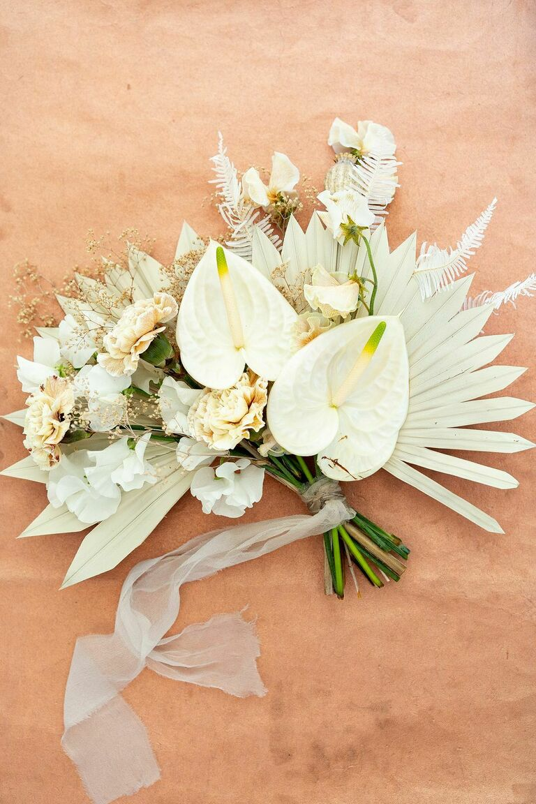 white bohemian wedding bouquet with anthurium carnations and painted sun palm leaves