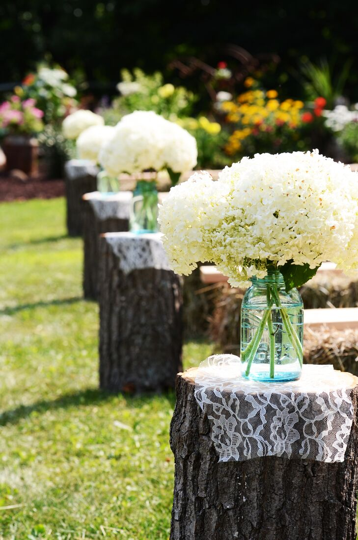 Jarred white hydrangeas were displayed atop wooden logs that lined the couple's outdoor aisle in Cushing, Wisconsin.