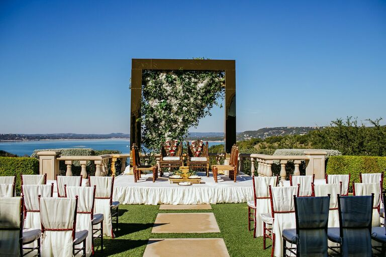 Outdoor wedding ceremony with mirrored arch and chairs with white linen covers