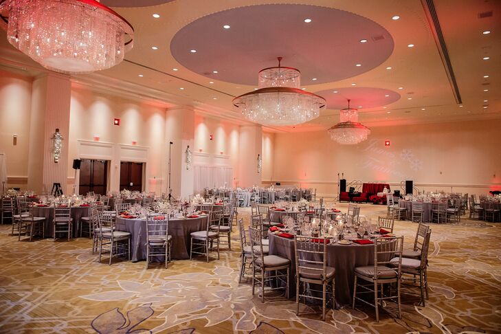 Red uplighting illuminated the ballroom and drew attention to the massive crystal chandeliers. Silver linens topped the tables and silver chiavari chairs kept the mood seasonally appropriate.