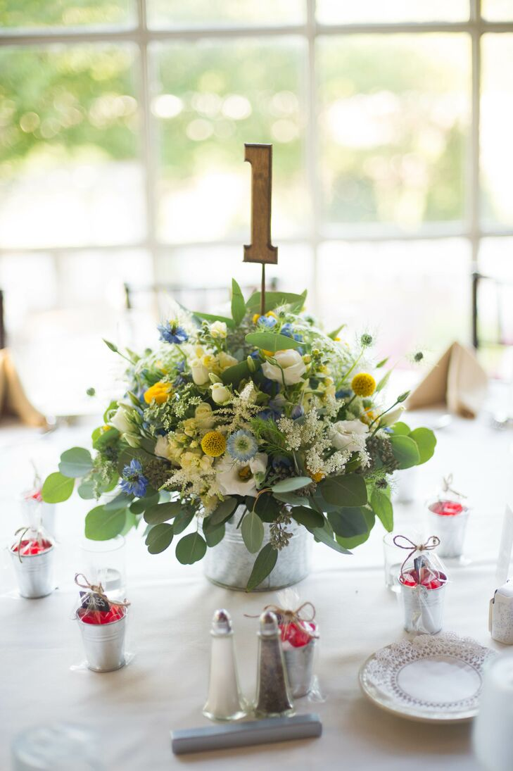 Silver pales, similar to fishing buckets, held lush arrangements of craspedia, eucalyptus and wildflower. Wooden table numbers stuck up front the centrepieces, directing guests to their seats.