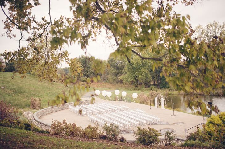 """""""We chose the location because it fit the number of people we were inviting  as well as had beautiful views of the Potomac, with rolling hills in the background and a barn that was just as beautiful on the inside as it was on the outside,"""" says Erin. For their waterfront ceremony, Dogwood Events helped to highlight the venue with rows of white folding chairs,  white balloons floating along the aisle and a white, shabby-chic white wedding arch."""