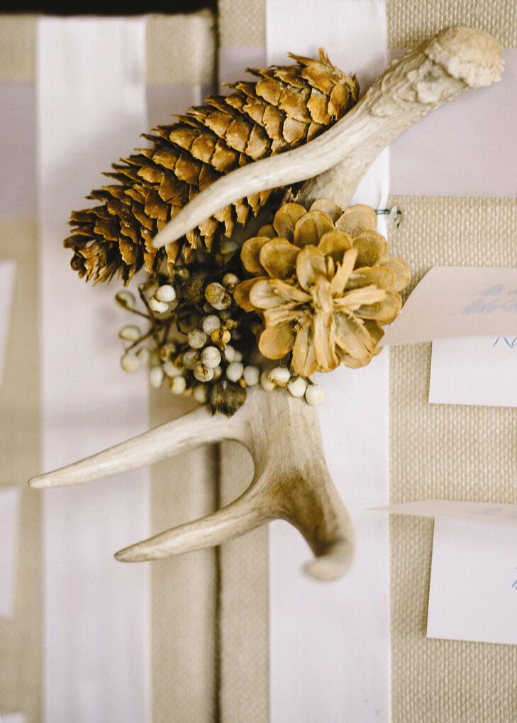 Pinecone and antler decor added some rustic charm to the couple's reception decor.