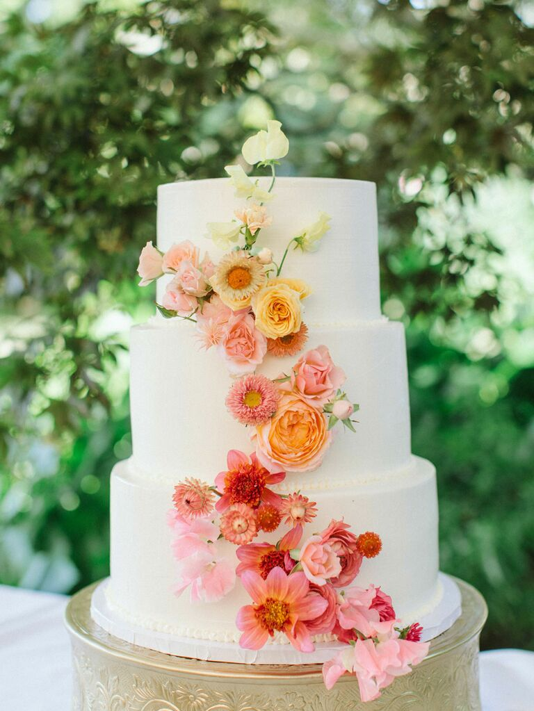 Three-tier white cake with ombré pink flowers at summer wedding
